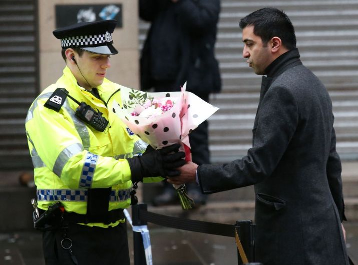 MSP Humza Yousaf passes flowers to a police officer close to the scene in George Square, Glasgow