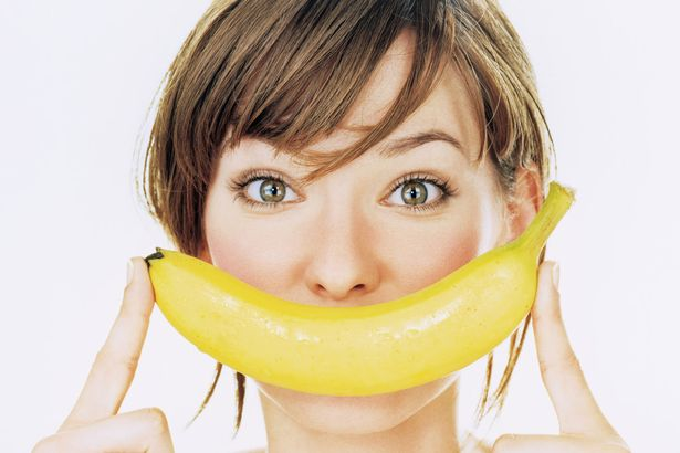Young woman holding banana over mouth