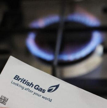 A person holding a utility bill in front of a gas hob