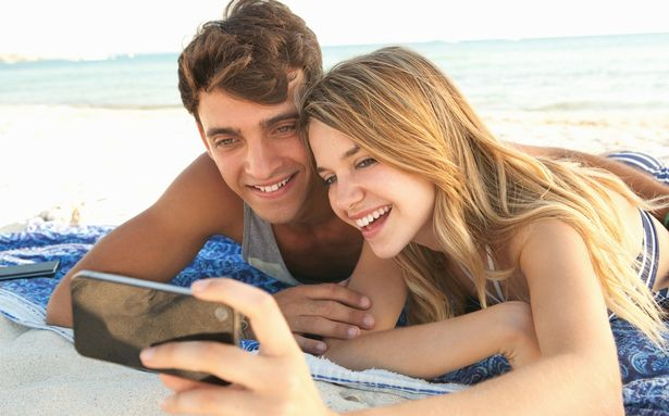 Young couple using smartphone technology to take a selfie on a beach holiday