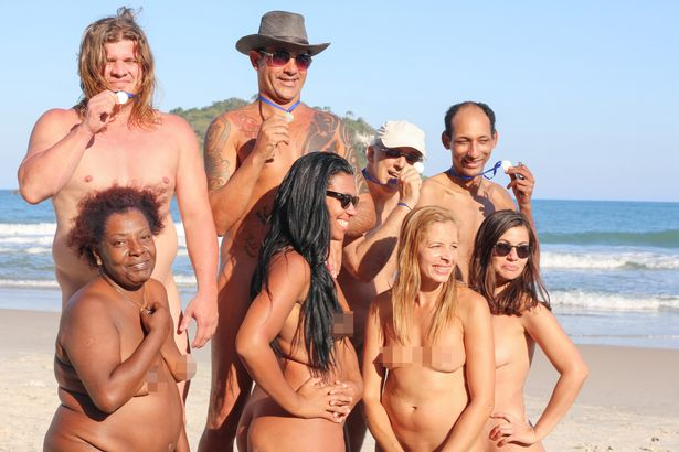 The group of Naked Olympians pose for a photo on the natural podium on Abrico Beach, Rios only nudist beach
