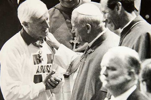 Jimmy Savile shakes hands with Pope John Paul II
