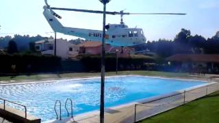Download Helicopter refills its water bucket from a public swimming pool Video