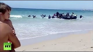 Download Boat with African migrants shocks sunbathers on Spanish beach Video