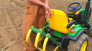 Download Farm Kid Driving Modified John Deere Toy Tractor With Cultivating Tines In The Garden Video