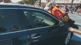 Download Car drives through group of immigration protesters Video