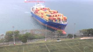 Download Container ship sails straight to shore by university football field Video
