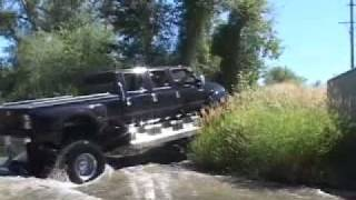 Download F-650 4x4 Six door pickup driving next to the road. Video