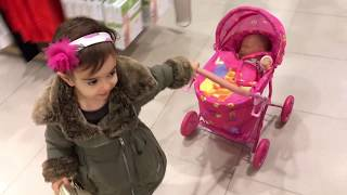 Download Little Girl Pushing Pink Stroller in Shopping Centre Video
