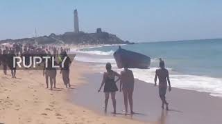 Download Spain: Migrants storm beach near Cadiz after jumping from boat Video