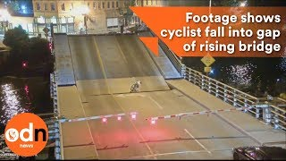 Download Shocking footage shows cyclist fall into gap of rising bridge Video