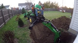Download Compact Tractor Backhoe digs hole for basement egress window Video