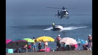 Download Police helicopter chases narco speedboat onto crowded beach Video