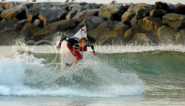 photo of a young surfer next to rudees inlet on virginia beach