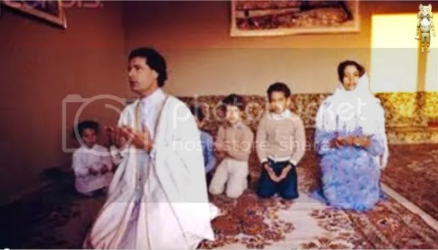 GADHAFI prays with his young family