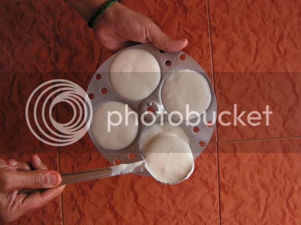 idli batter being filled in idli maker