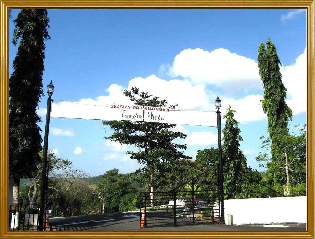View of the main entrance gate to the premises of the Hindu Temple.  The sign reads, Thank you for visiting us - Hindu Temple.  Notice the lush vegetation around the area of the temple.