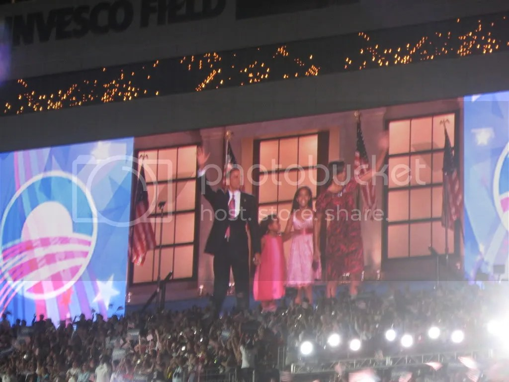 A projection screen at Invesco Field shows Barack and Michelle Obama, with their daughters, at the end of the evening.