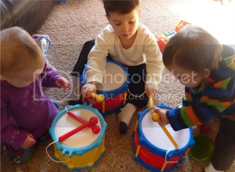 three children playing drums