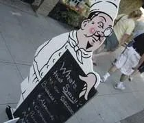 A little wooden chef advertising for Macs Fudge