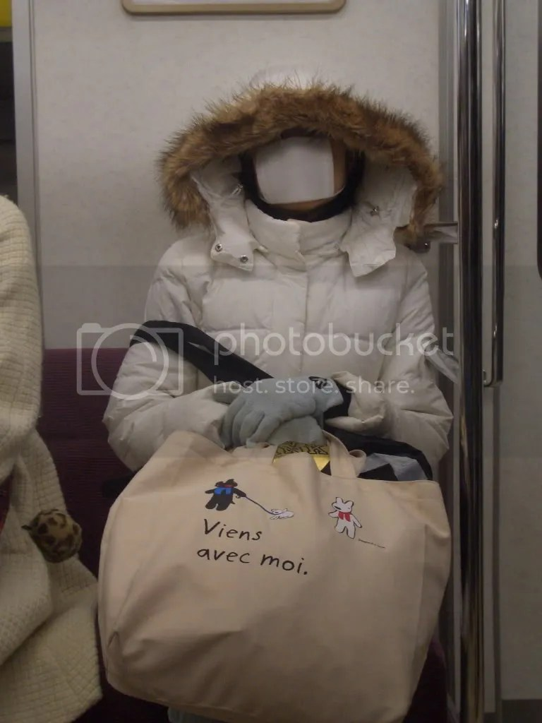Woman ready to face the cold sits on the train.