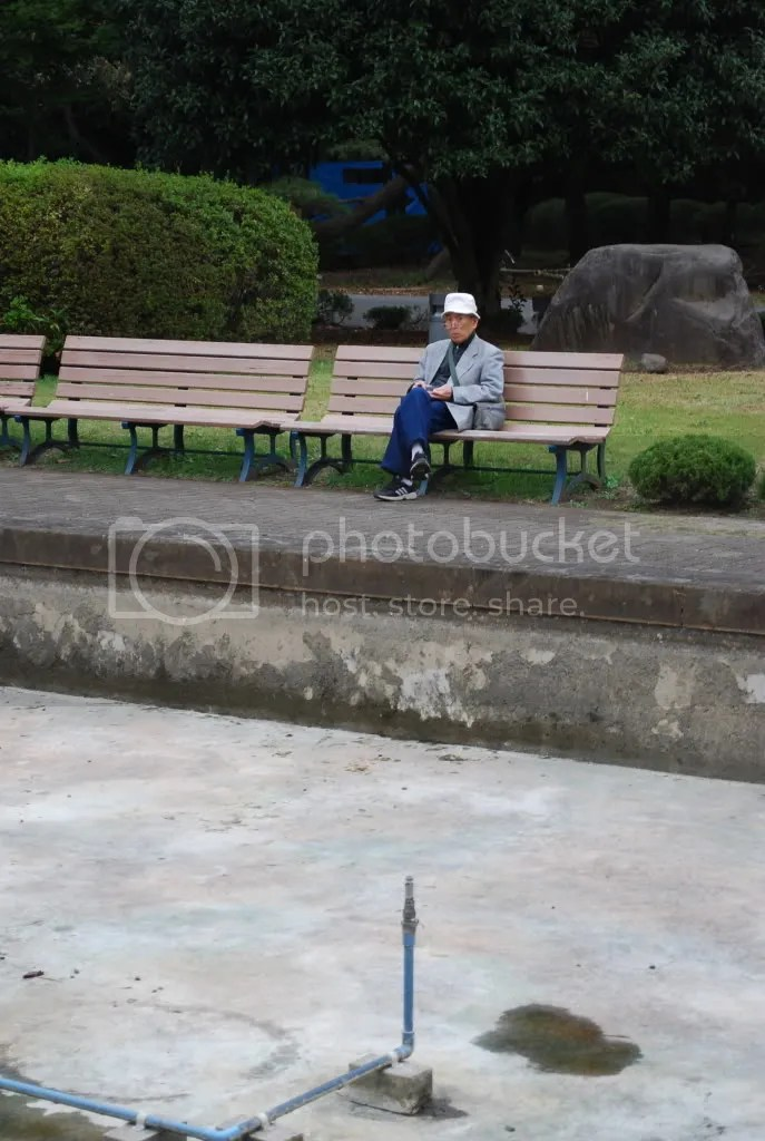 an old man rests on the benches in front of the empty fountains