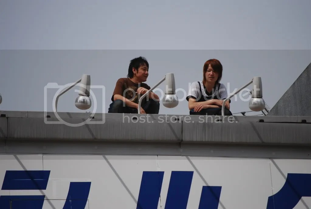 People watch from the roof of a 100 yen store