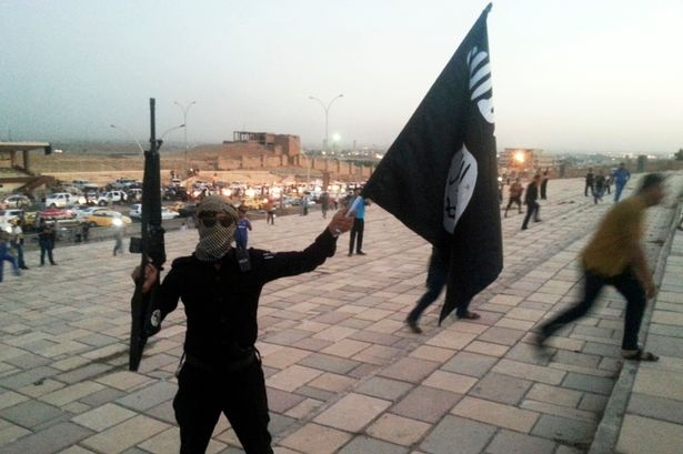 A fighter ISIL holds an ISIL flag and a weapon in Mosul