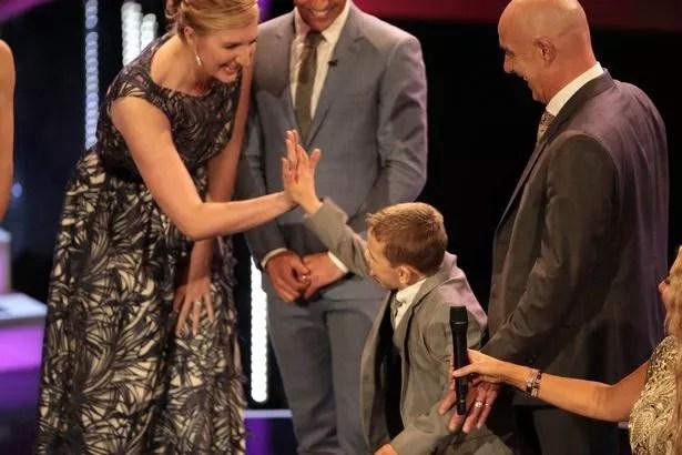 aChild of Courage award winner Bailey Matthews high-fives Rebecca Adlington