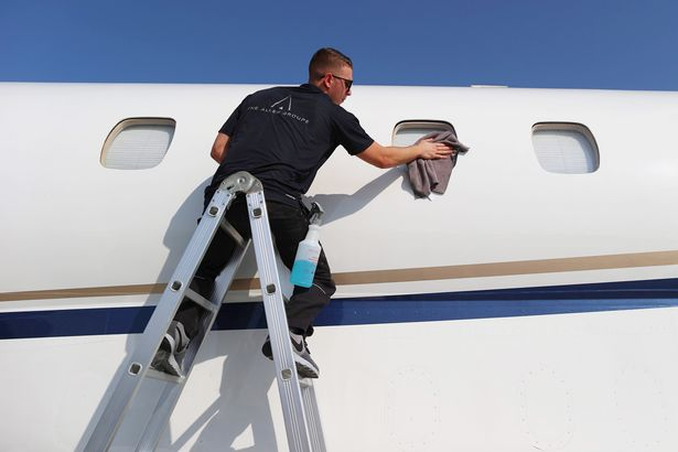 An employee of Allen Groupe polishes the passenger windows of an Embraer SA Legacy jet