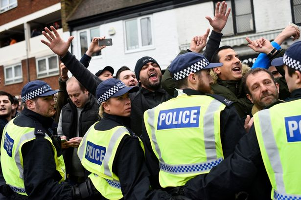 Police form a line as fans chant outside the ground before the match