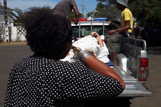 A photo taken by a witness at the scene shows a victim being loaded on a pick-up truck