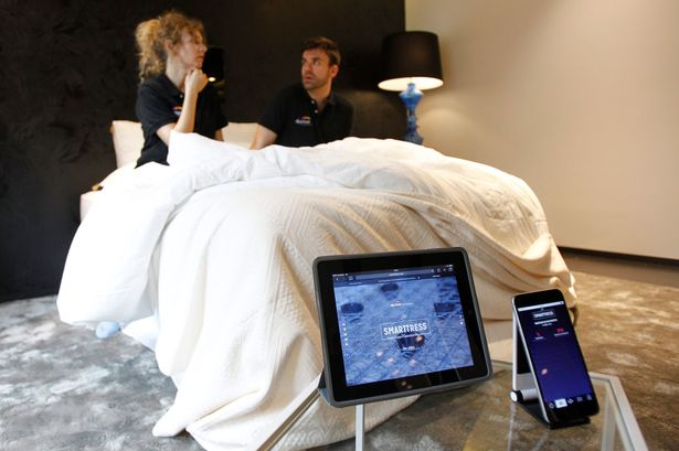 Two people pose on the Smarttress mattress