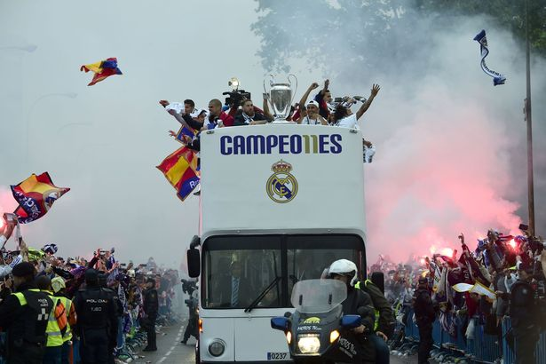 Fans surround the bus as Real Madrid players hold up the trophy celebrating the team's win on Plaza Cibeles in Madrid on May 29, 2016
