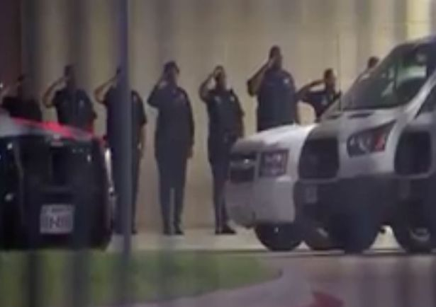 Dallas officers pay their respects as the bodies of the colleagues killed are transported