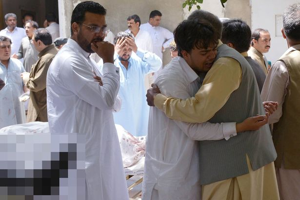 Pakistani relatives mourn next to bodies of victims after a bomb explosion at a government hospital premises in Quetta