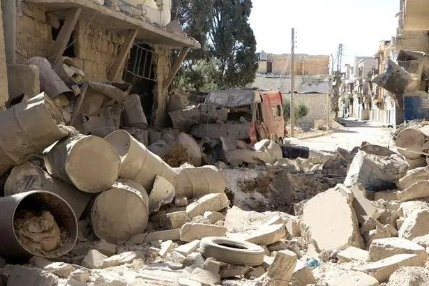 A los restos de los edificios destruidos por el hospital Sahra se ven después de una huelga barril bomba al paso de las fuerzas del régimen sirio sobre el barrio Sahur de Alepo, Siria
