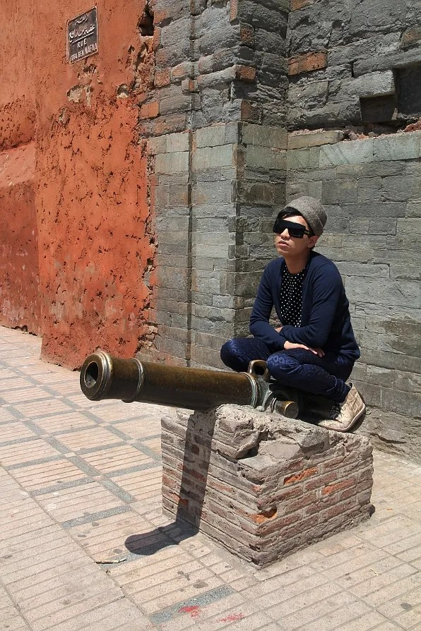 Bryanboy sitting on top of an old canon in Marrakech, Morocco