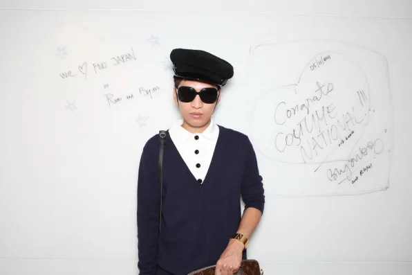 Bryanboy posing in front of the sign he made for Costume National