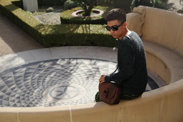 Bryanboy sitting with his Reed Krakoff bag at the Herb garden of Getty Villa in Malibu