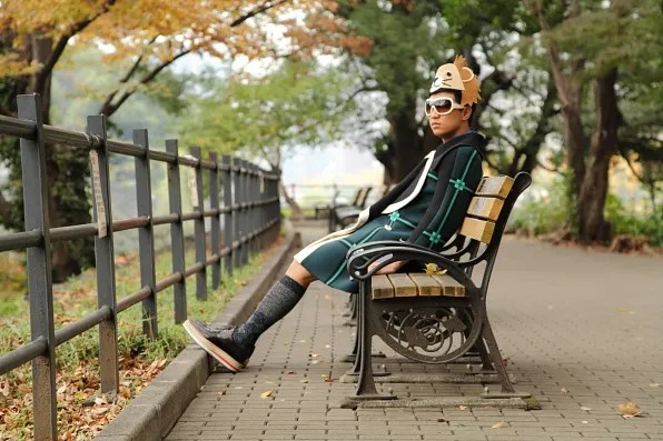 Bryanboy wearing a Prada coat sitting on a bench at Hibiya park