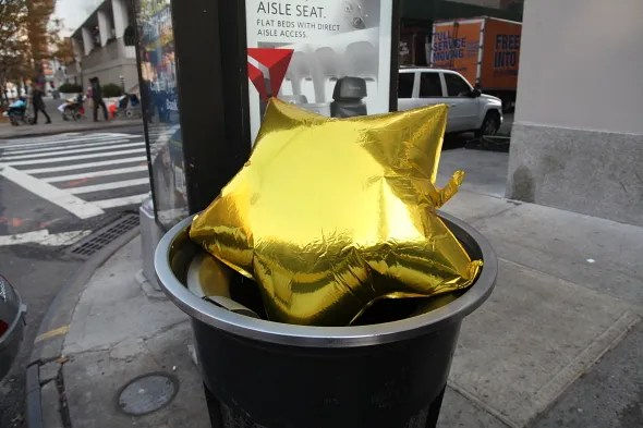Gold star balloon in a trash can
