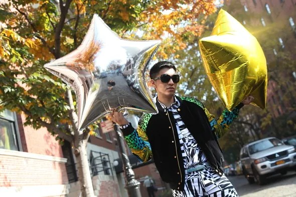 Bryanboy holding silver and gold star balloons