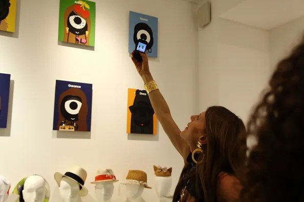 Anna dello Russo taking a photo of her portrait by Darcel at Colette, Paris