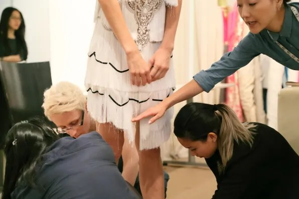 Marchesa staff discussing final alterations and hem lengths