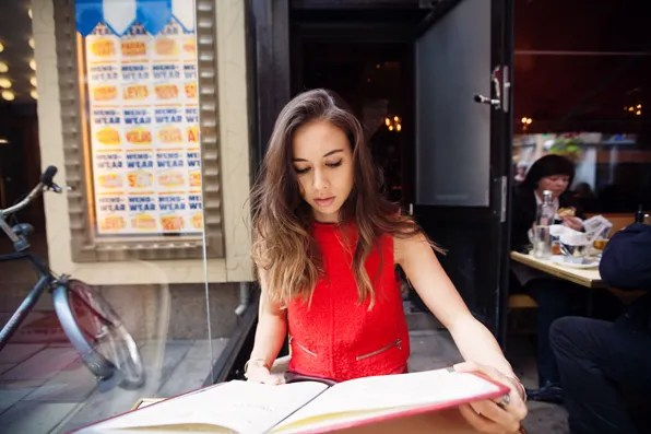 Rumi Neely browsing the menu at Zink Grill in Stockholm