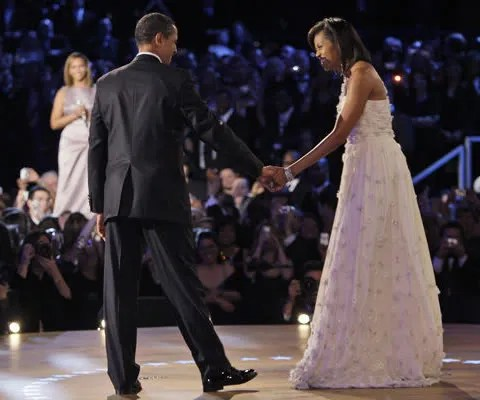 Barack and Michelle Obama dancing. Michelle Obama's white dress was designed by Taiwanese-American designer Jason Wu.