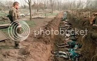 Un soldado ruso observa los cuerpos de civiles chechenos asesinados durante el invierno y enterrados en una fosa común. Están siendo exhumados para su identificación en el cementerio de Grozni. 31 de marzo de 1995. Fotografía de Alexander Nemenov.