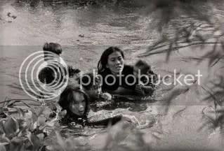 Una madre y sus hijos cruzan a nado un rio escapando del bombardeo del Ejercito de los Estados Unidos. Imagen tomada por Kyoichi Sawada en la comuna de Loc Thuong, situada en la provincia survietnamita de Binh Dinh. Septiembre de 1965. Guerra de Vietnam.