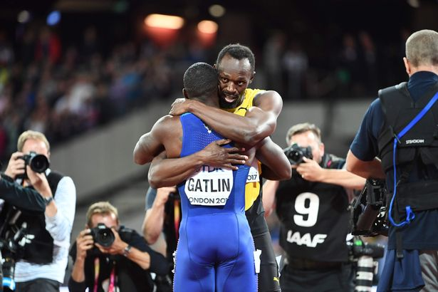 Jamaica's Usain Bolt (R) embraces US athlete Justin Gatlin after the final of the men's 100m